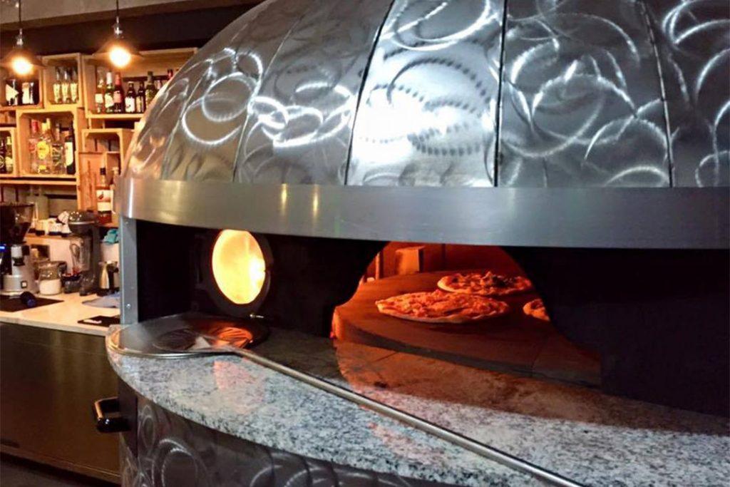 Forno a legna e a gas rotativo con pizze dentro